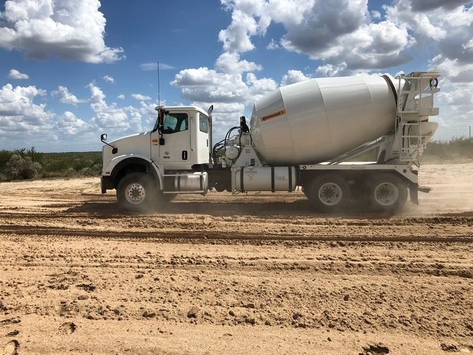 A mixer fitted with Conti HAC 3 wide flotation tires on the steer axle and HDC 3 retreads on its trailing axles navigates a soft sand course on the Continential proving grounds in Uvalde, Texas.