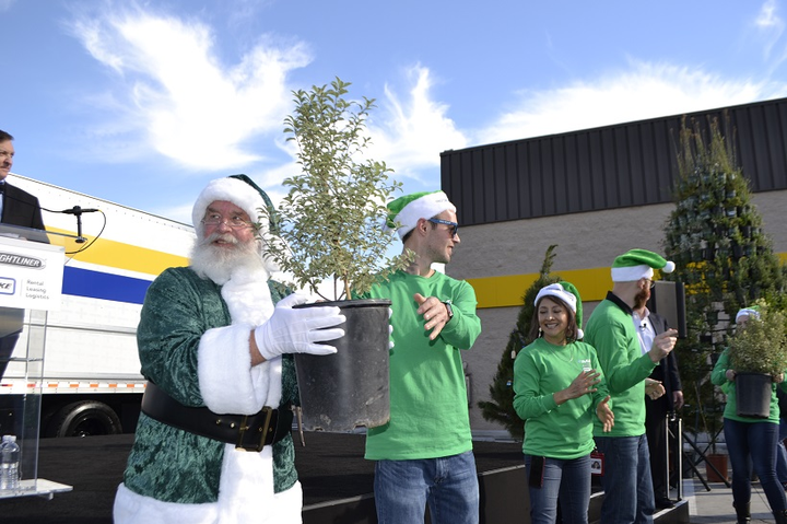 A man in a green Santa suit and members of the Daimler team loaded small trees onto ane eM2 bound for the hills that were burned in Los Angeles's recent wildfires. 
