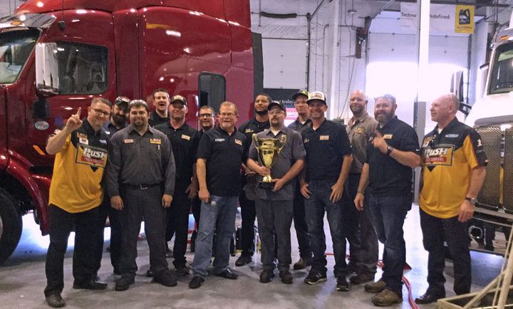 Rush Truck Center past champions, Rusty Rush (center), and the Stewart-Hass Racing No. 14 pit crew celebrate a photo-finish tech competition at Rush's Dallas dealership.