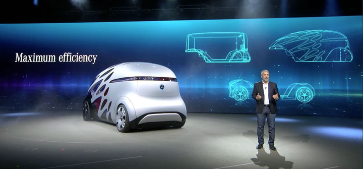 Slide shows the interchangeable cargo/passenger body concept of the Urbanetic as the people-moving version rotates on the stage in the foreground.  - Screen capture from Mercedes-Benz video at IAA press conference