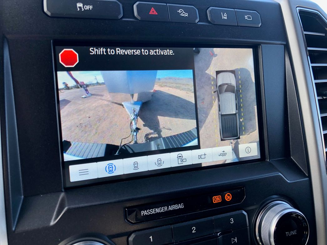 An enhanced Trailer Reverse Guidance system features a screen with several camera/view...