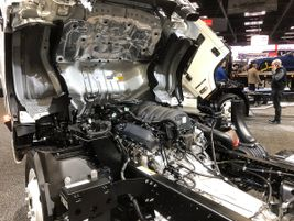 A Class 4 Isuzu NPR HD cab tilted up revealing the new 6.6L V8 gasoline engine introduced this...