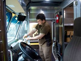 A UPS drivers uses hand sanitizer.