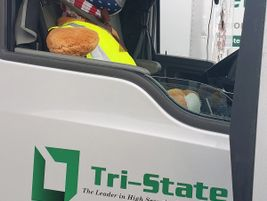This teddy bear riding shotgun not only has his safety vest on, but also a mask to protect...