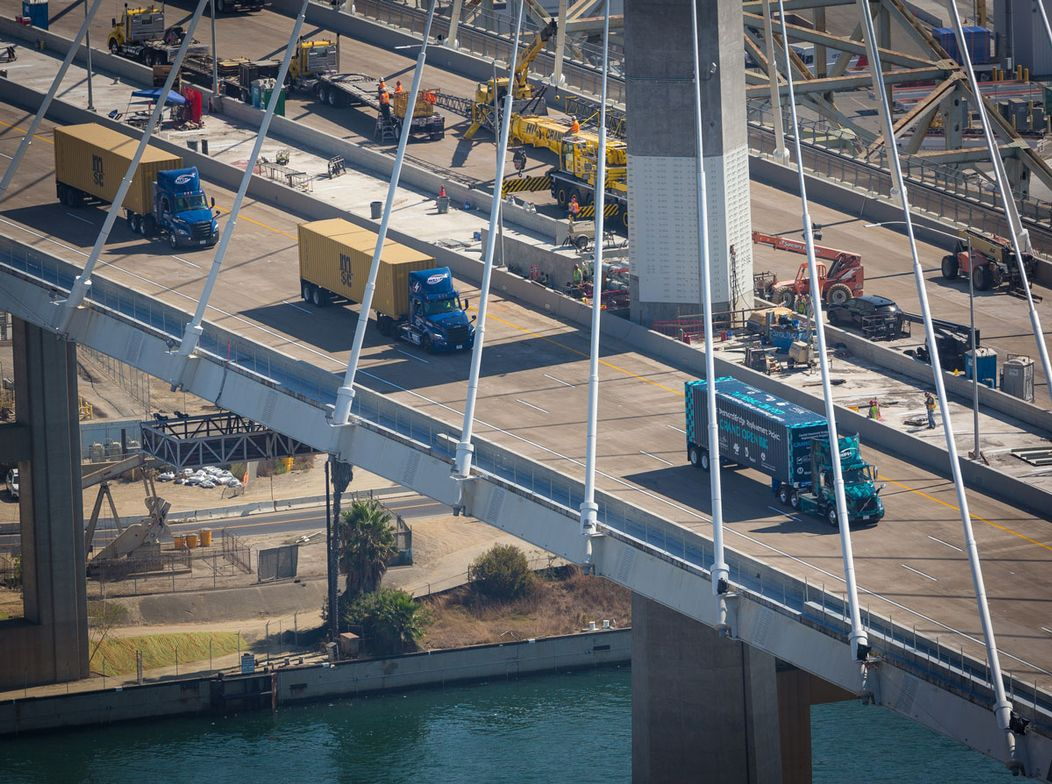 "The ""first drive"" over the bridge was led by 30 cargo trucks representing the port's terminals..."