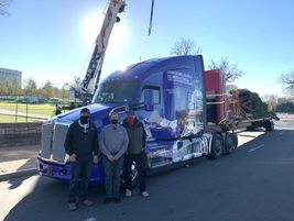 Apex drivers Butch Hanna and Theron Schmalzried during the tree unloading process.