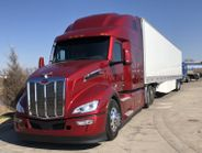 The Legacy Red New Model 579 waits for the second leg of its HDT test drive at a Texas truck stop.