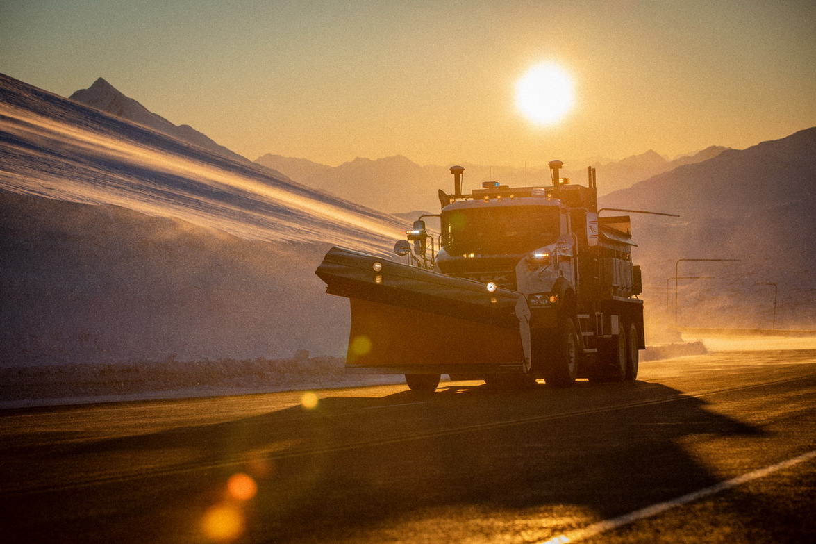 One of the Mack Granite plows driving over Thompson Pass at sunrise.