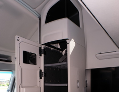 Above the fridge on the passenger side is a tall cabinet with adjustable shelving or a wardrobe...