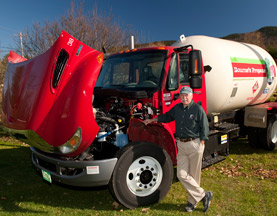 Bourne's Energy chose to lease two hybrids from Ryder, including this propane-hauling truck, displayed next to President Peter Bourne.
