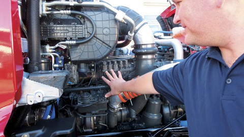 Peterbilt service engineer Chadd Christian's fingers indicate sensors for EGR, turbocharger and...