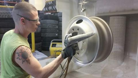 "Juan Klinehoffer, the ""wheel man"" at Bob Sumerel Tire in Zanesville, Ohio, air-sprays positively..."