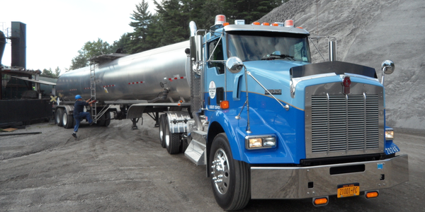 The Kenworth T800 waits quietly as hot liquid asphalt is pumped from the Etnyre tanker, and...