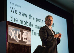 XRS CEO Jay Coughlan announcing the company's name change to XRS Corporation and its new all-mobile platform, also called XRS, during the XUE opening session on Aug. 13.