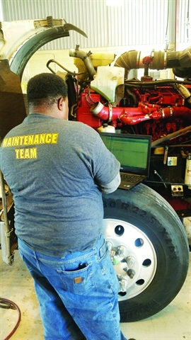 A technician uses a laptop at Dillon Transport, where data helps the Illinois-based carrier stay on top of a fleet that's about half natural gas powered. Photo: Evan Lockridge