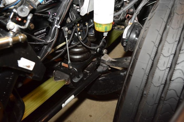 An air-over-composite-spring front suspension allows for a lower ride height at highway speed while maintaining roll stiffness.