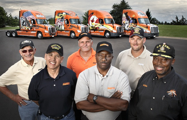 Schneider National has had active programs recruiting former military drivers like these for years. In the background are its Ride of Pride trucks, special veteran-themed trucks built by Freightliner to participate in the Rolling Thunder Ride of Pride on Memorial Day as well as in other events.