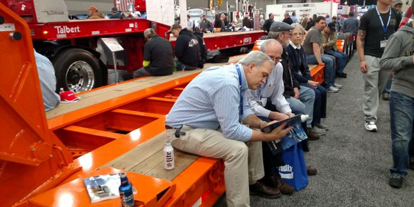 The Mid-America Trucking Show featured many trailer makers. Showgoers here make use of a lowbed...