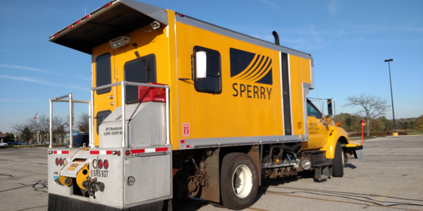 Sperry Rail Services truck with specialized body and equipment is parked outside a Kroger...