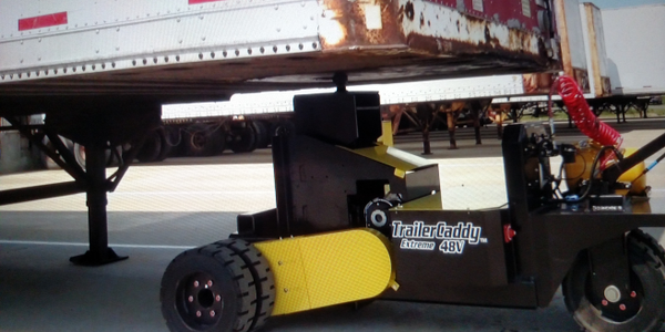 Compact walk-behind machine slips under a trailer's nose, lifts it, and pulls it away. Optional...