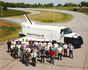 Mack employees built the simulated Space Shuttle Blake from an old military bus. They pose in 1995.