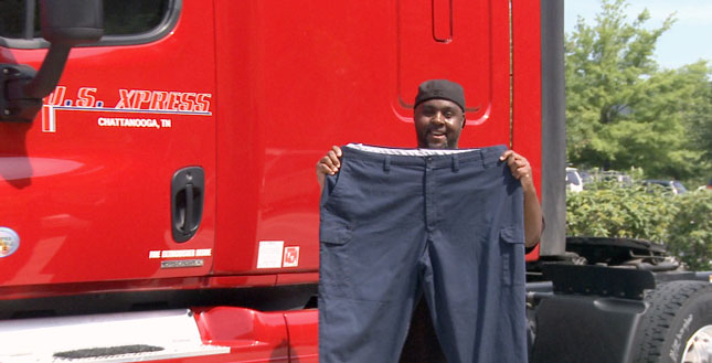 Doug Robinson holds up a pair of pants that's too big now that he's had success losing weight.
