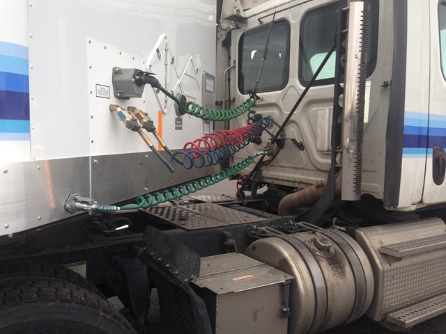 "Lower green cord is the ""stinger"" that carries power and a return ground line to trailer batteries that operate the liftgate. Connector cord should remain plugged in to keep a load on the line while its circuit is tested. Photo: Con-Way Freight"