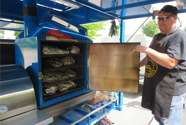 Robert Smith from Pitt's and Spitt's shows off BBQ brisket waiting for lunch in the custom-made Shell Rotella rolling barbecue pit.