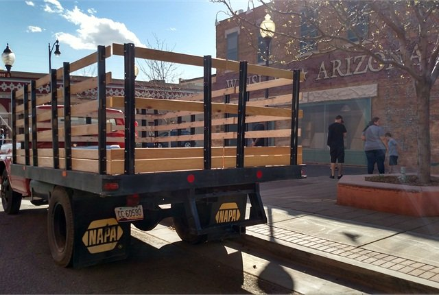 Steel flatbed body wears tall stakes with wooden slats. Imagine what it hauled in its day.