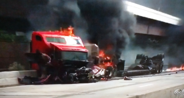 Tractor's frame is twisted and its hood ripped awayas flames engulf its rear. But the cab appears intact and motorists were able to pull out the driver and his dog.