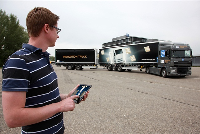 The tractor's steering and movement are remotely controlled by a man with special app on a tablet computer. It sends the pup trailer in the proper path, and the semitrailer and tractor follow along, guided by the ZF app's computations. Photo: ZF Freidrichshafen AG