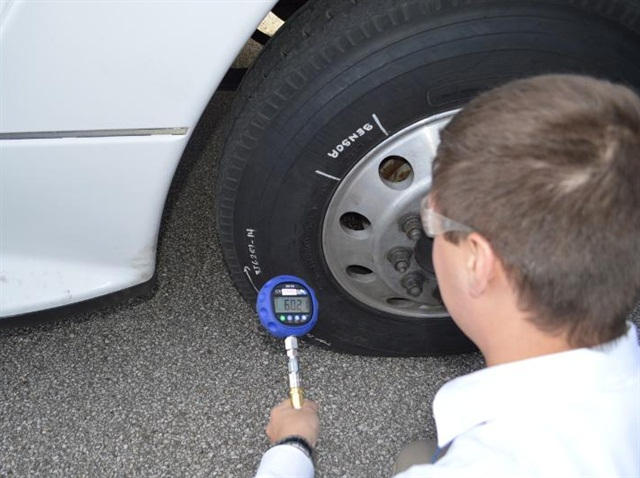 A Goodyear Tire & Rubber Company tire test engineer checks the pressure on a tire equipped with the company's Air Maintenance Technology. Photo: Goodyear.