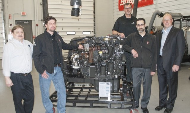 Presenting the donated engine from Berger Dealer Group are service managers Joe Kook (second from left) and Mike Peters (second from right). Photo courtesy of Baker College.