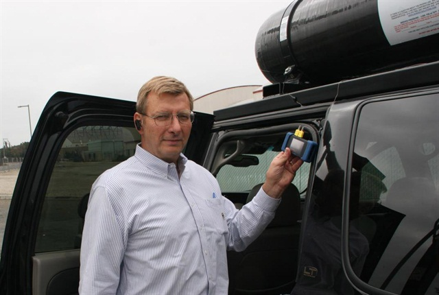 Gary Fanger, COO and team leader of Cenergy Solutions' ANG project, installs carbon-filled tanks atop a Chevrolet Suburban used in testing. For common use, the tanks would have protective caging or be installed inside. Photo courtesy Cenergy