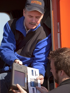 A Schneider driver hands an enforcement officer his Omnitracs unit to check his electronic logs. The proposed rule would make paper printouts an option.