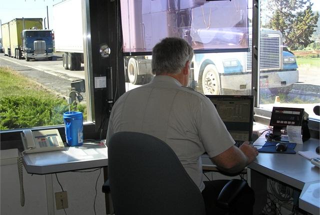 An Oregon DOT motor carrier enforcement officer weighs a truck as a it passes through a Port of Entry.