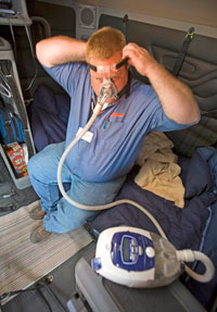 A driver for Schneider National, which has been an industry leader in sleep apnea testing, demonstrates the equipment used to treat the condition.