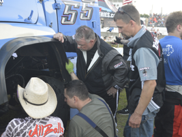 Craig Kruckeburg and the Minimizer pit crew check damage on the Ford truck.