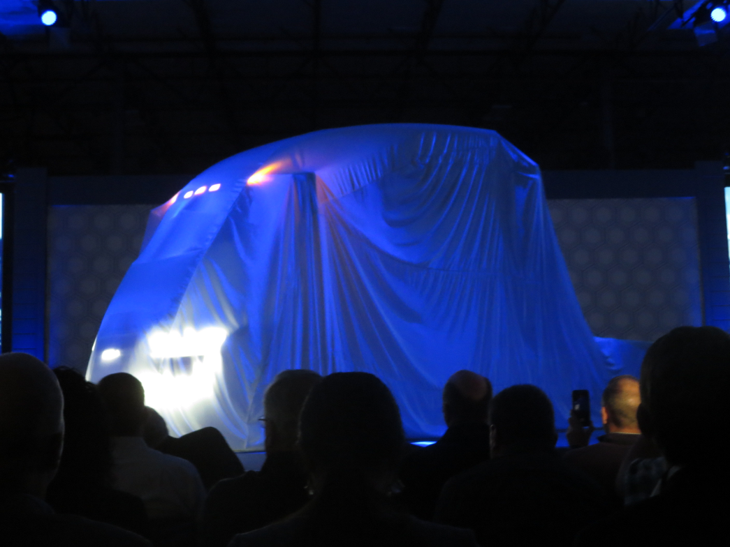 The Nikola One prototype rotates on a turntable with the veil still in place.