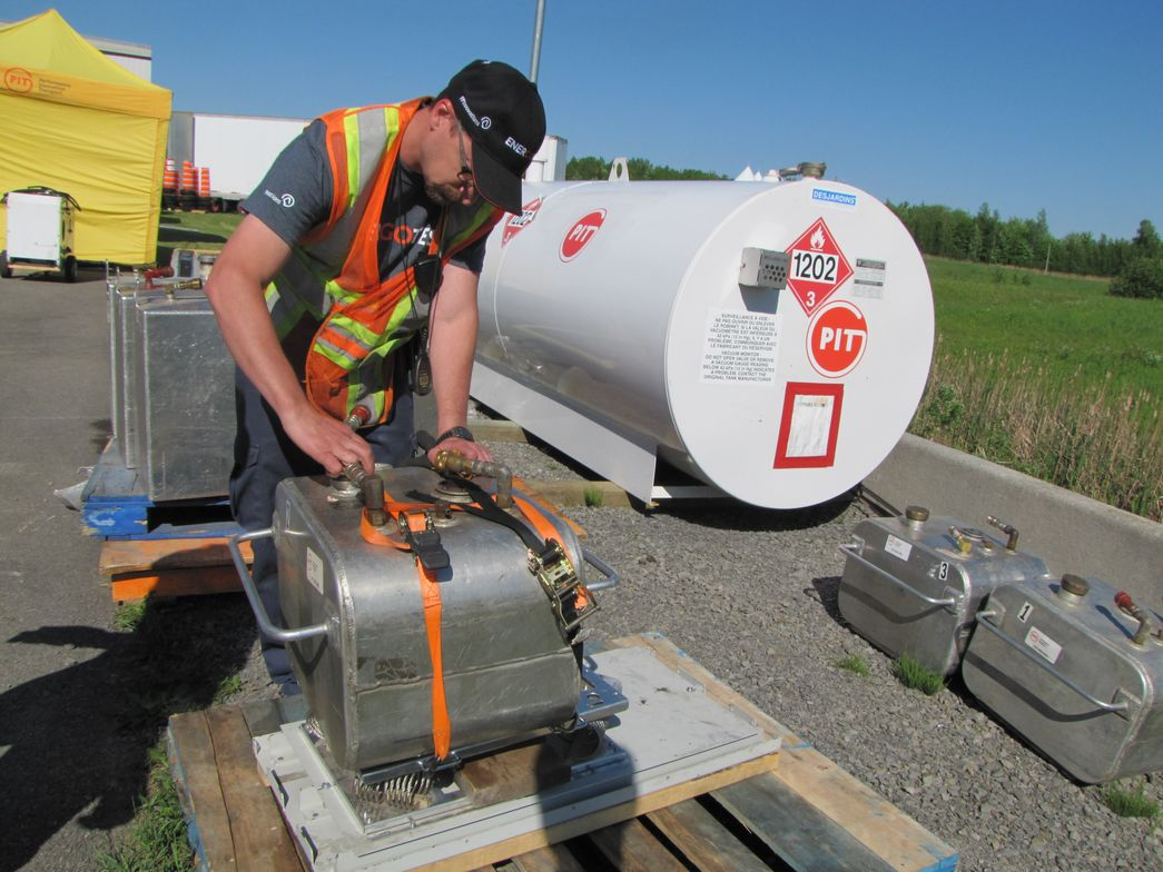 Steve Mercier, PIT Group engineer, fueling up auxiliary tanks that are used to accurately...