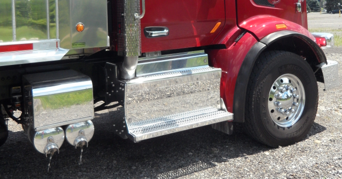 Exhaust aftertreatment equipment is behind the steps on the right side. A nose-mounted convex...