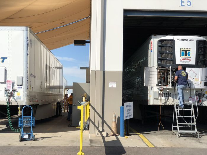 On the trailer side of SwiftTech, a technician looks at a Thermo King refrigerated unit.
