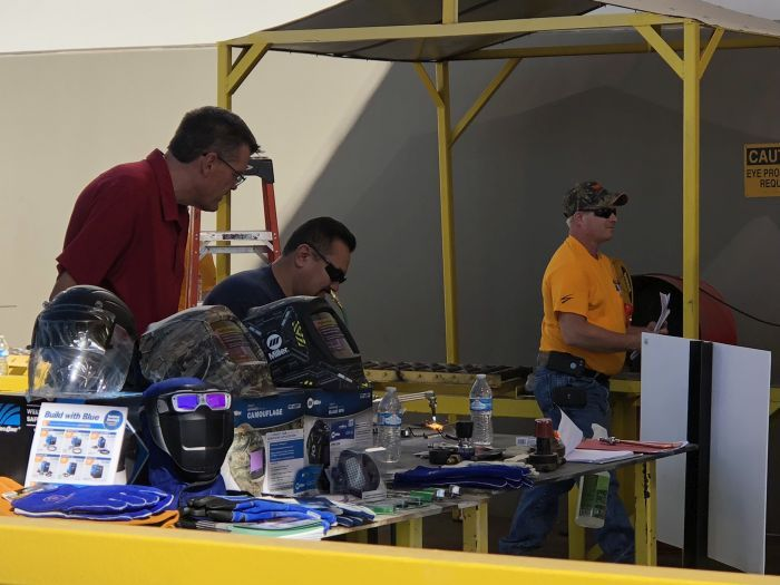 A technician demonstrates welding skills with a torch as a judge watches closely.