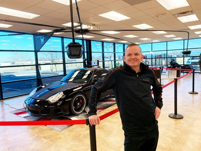 Black Widow founder and CEO Jason Hauk with his multi-armed digital camera system that can prepare vehicles for the digital auction and dealer marketplaces. - Photo: Black Widow