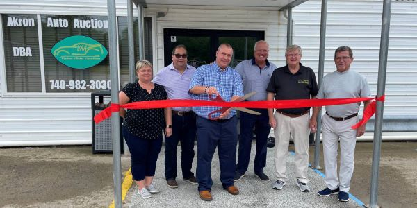 Chad Bailey cuts the ribbon June 3 at the first official sale following Akron Auto Auction's...