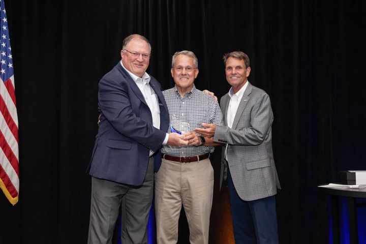 Frank Hackett (center), the retired CEO of the National Auto Auction Association, accepts award from Tony Long, IARA executive director, and President Seger. - Photo: IARA