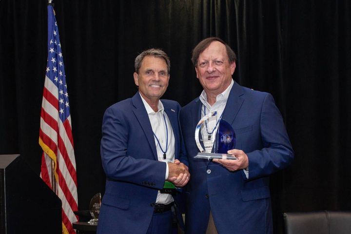 Cox Family Office CEO Sandy Schwartz (R) accepts his award from IARA President Paul Seger. - Photo: IARA