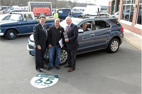 (L – R) Dan Kennedy, manager for GM Remarketing; Todd Caputo, owner of Sun Chevrolet, Inc.; and Larry Tribble, Southern Auto Auction owner and president, pose in front of the 14 millionth remarketed GM vehicle, a 2011 blue Chevrolet Equinox, which Caputo purchased during a sale on March 28.