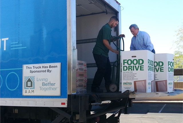 Ready Auto President Jerry Tassone, right, helps load food donations for United Food Bank.