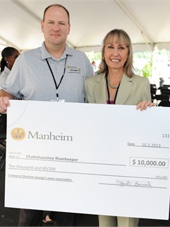As part of the anniversary celebration Manheim made the donation to Chattahoochee Riverkeeper. Manheim Georgia General Manager Mike Benfield presents $10,000 donation check to Chattahoochee Riverkeeper Executive Director Sally Bethea, right.